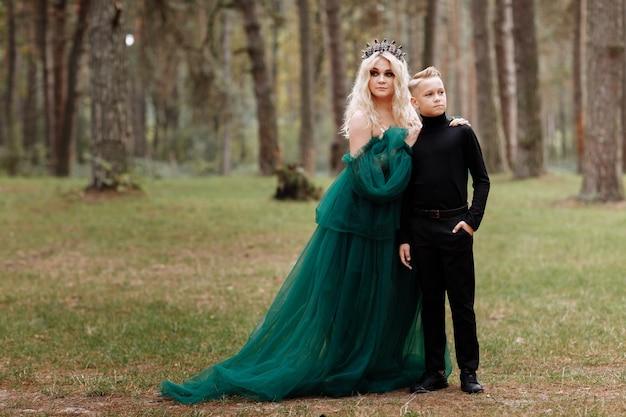 Jonge mooie blonde vrouw koningin met jonge jongen in zwarte outfit. prinses moeder loopt met zoon. herfst groen bos mysticus.