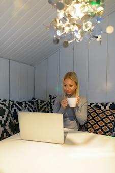 Jonge mooie blonde vrouw met behulp van laptop terwijl het drinken van koffie thuis
