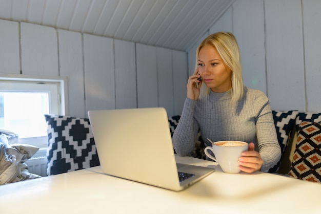 Jonge mooie blonde vrouw met behulp van mobiele telefoon met koffiekopje en laptop thuis