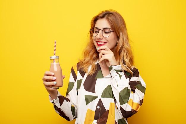 Jonge mooie blonde vrouw met een milkshake