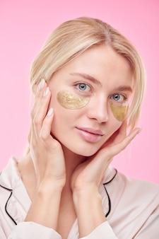 Jonge mooie blonde vrouw met gouden revitaliserende patches onder de ogen die voor haar gezicht zorgen