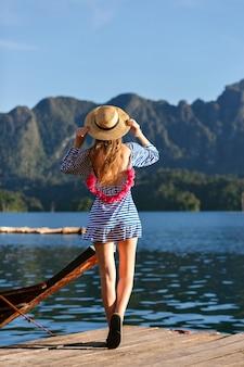Jonge mooie blonde vrouw met lange haren, vintage hoed en heldere sexy trendy jurk dragen kijkt naar de bergen en het meer, laat haar hand zien, geweldige zomeravonturen.