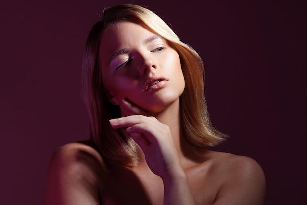 Jonge mooie blonde vrouw met schone stralende huid geniet van het aanraken van de huid van haar gezicht, een portret met paarse toning en trendy naakt make-up op een roze achtergrond