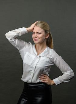 Jonge mooie blonde vrouw met stress en hoofdpijn op een grijze achtergrond. mooie vrouw met hoofdpijn.