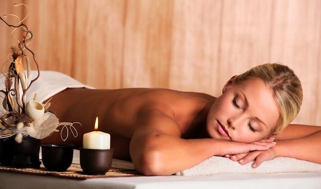 Jonge mooie blonde vrouw ontspannen in de spa salon