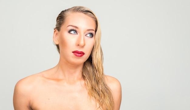 Jonge mooie blonde vrouw shirtless als gezondheids- en schoonheidsconcept tegen witte ruimte