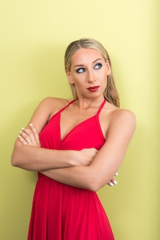 Jonge mooie blonde vrouw tegen groene muur