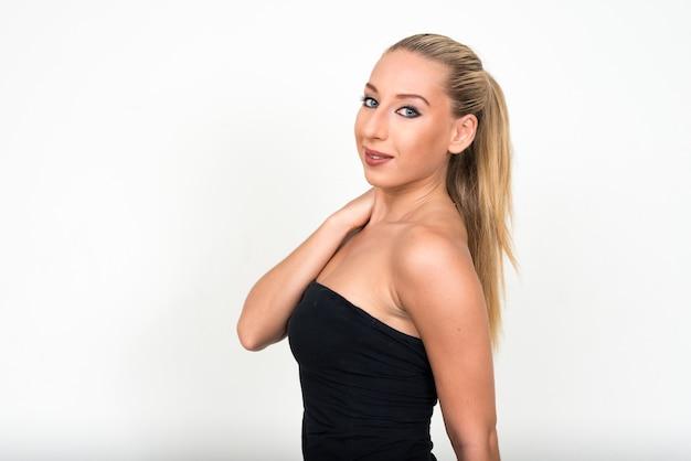 Jonge mooie blonde vrouw tegen witte muur