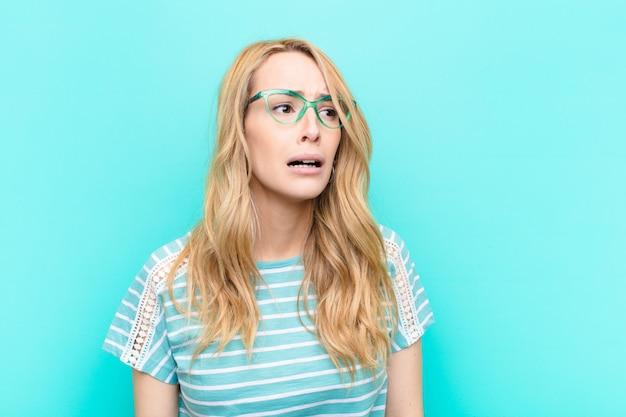 Jonge mooie blonde vrouw verdrietig en zeurderig met een ongelukkige blik, huilen met een negatieve en gefrustreerde houding tegen egale kleurenmuur