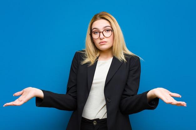Jonge mooie blonde vrouw verhogen palm aan voorhoofd denken oeps, na het maken van een domme fout of herinneren, zich dom voelen tegen flat