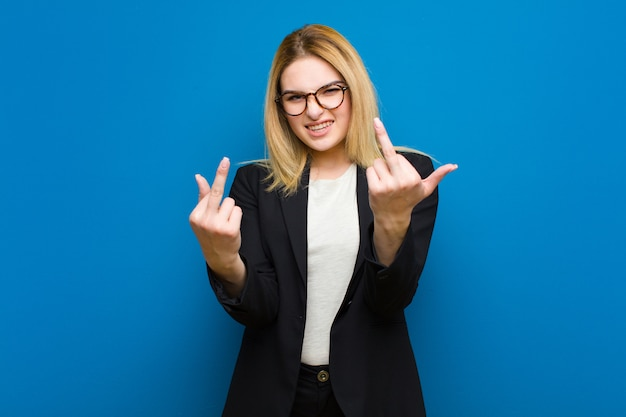Jonge mooie blonde vrouw voelt provocerend, agressief en obsceen, flipping de middelvinger, met een rebelse houding op een vlakke muur