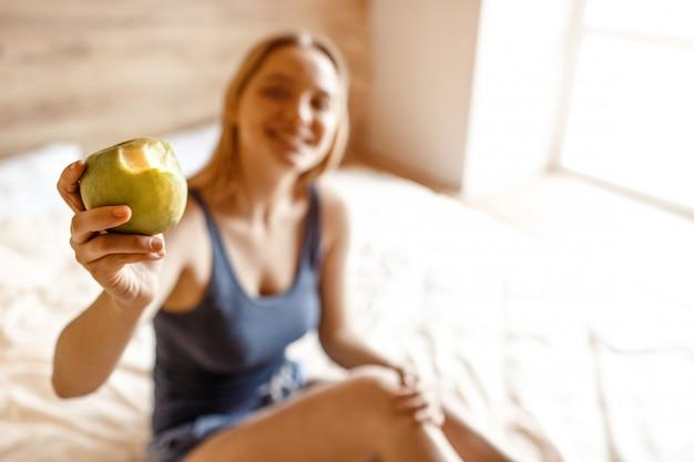 Jonge mooie blonde vrouwenzitting in bed in ochtend. onscherpe achtergrond. model houd gebeten appel en toon het aan camera. vrolijk positief. daglicht.