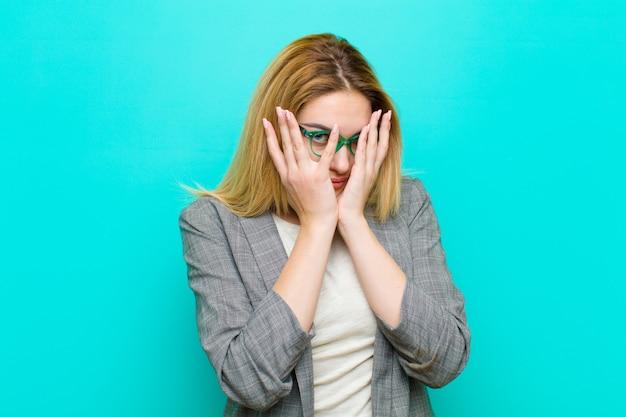 Jonge mooie blondevrouw die bang of beschaamd voelen glurend of spionerend met ogen half bedekt met handen tegen vlakke muur