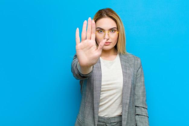 Jonge mooie blondevrouw die ernstig, streng, ontevreden en boos tonend open palm kijkend eindegebaar maken tegen vlakke muur
