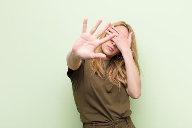 Jonge mooie blondevrouw die gezicht behandelen met hand en andere hand vooraan zetten om camera tegen te houden, die foto's of beelden over kleurenmuur weigeren