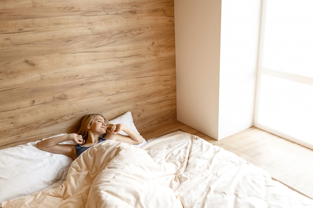 Jonge mooie blondevrouw die in bed in ochtend liggen. zij wordt wakker. model stretch handen omhoog. slaperige schoonheid. alleen in de kamer. daglicht.