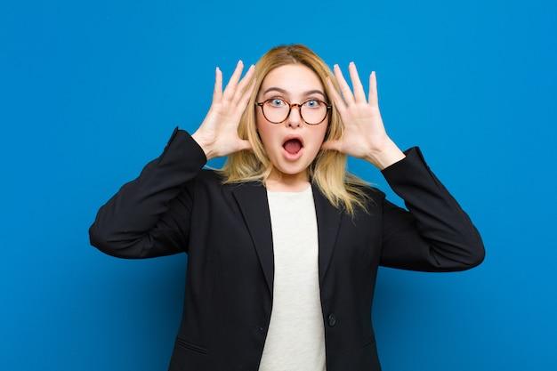 Jonge mooie blondevrouw die met handen omhoog in de lucht gillen, woedend, gefrustreerd, gestresst en boos tegen vlakke muur voelen