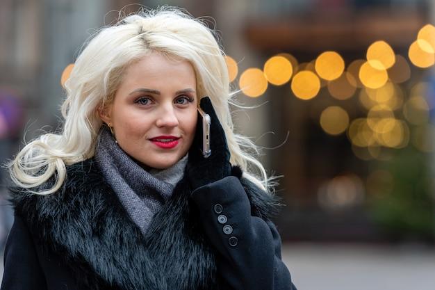 Jonge mooie blondevrouw die op smartphone tegen feestelijke lichten spreken.
