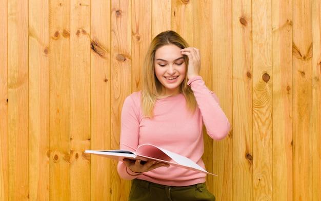 Jonge mooie blondevrouw met boeken over houten muur