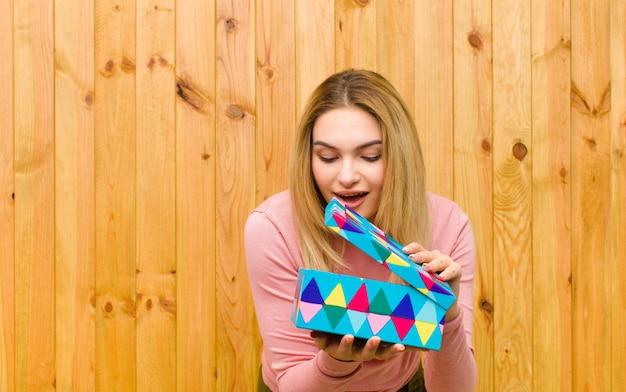 Jonge mooie blondevrouw met een houten muur van de giftdoos