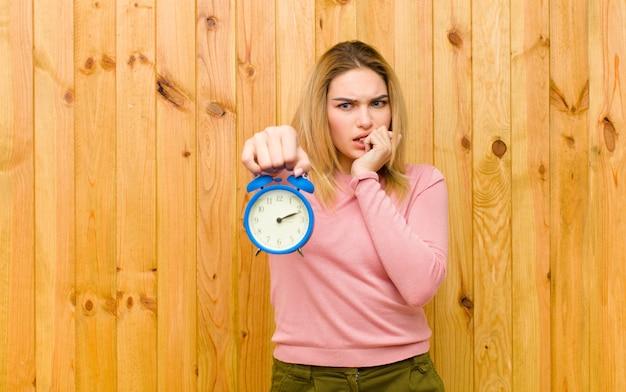 Jonge mooie blondevrouw met een wekker tegen houten muur