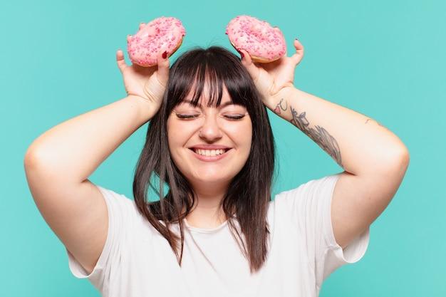 Jonge mooie bochtige vrouw gelukkige uitdrukking en met een donut