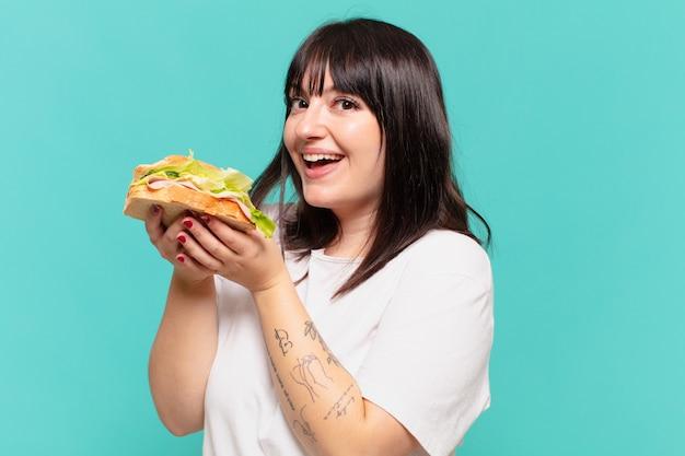 Jonge mooie bochtige vrouw gelukkige uitdrukking en met een sandwich
