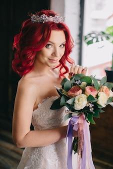 Jonge mooie bruid die een boeket houdt en dichtbij het venster op het hok staat