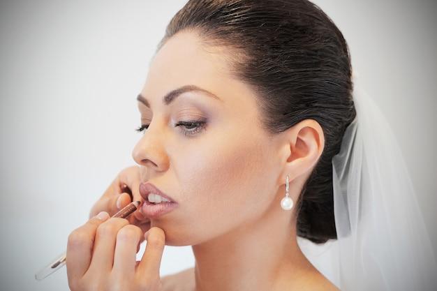 Jonge mooie bruid die huwelijksmake-up als make-upartiest toepast. ochtendvoorbereiding. handen dicht bij elkaar bij het gezicht. lip make-up.