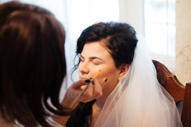 Jonge mooie bruid die huwelijksmake-up door grimeur toepassen