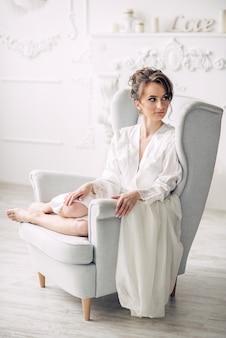 Jonge mooie bruid in een zachte witte robe zittend op een stoel in een helder interieur met kaarsen op de achtergrond