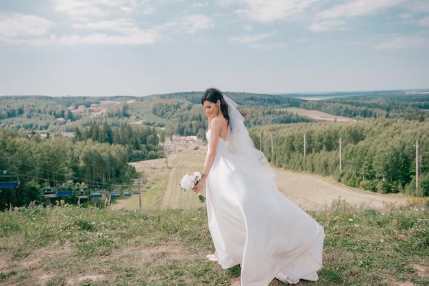 Jonge mooie bruid in witte trouwjurk poseren op een heuvel in de natuur.