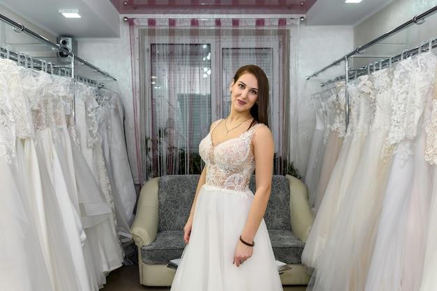 Jonge mooie bruid jurk en sluier kiezen in salon