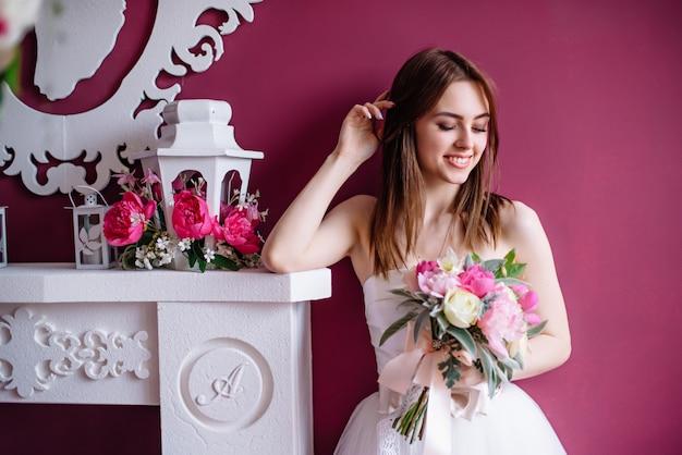 Jonge mooie bruid met een boeket van roze pioen in de buurt van de muur