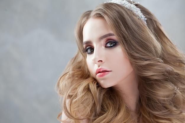 Jonge mooie bruid met luxe krullen. bruiloft kapsel met tiara.