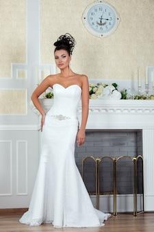 Jonge mooie bruid permanent in de buurt van open haard in luxe trouwjurk