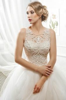 Jonge mooie bruid, vrouw in lange witte trouwjurk op whit
