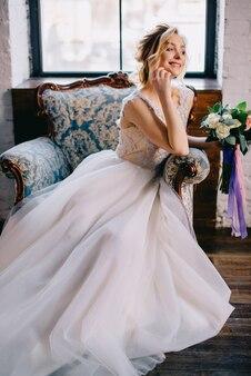 Jonge mooie bruid zittend in een stoel en glimlachen, close-up