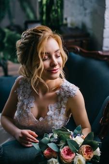 Jonge mooie bruid zittend in een stoel met gesloten ogen, close-up