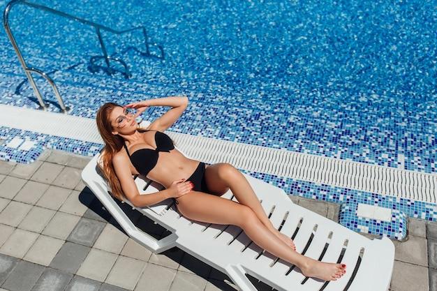 Jonge mooie bruinharige vrouw in een zwarte zwembroek en zonnebril liggend op de ligstoel bij het zwembad en zonnebaden.