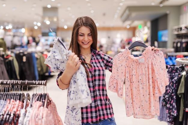 Jonge mooie brunette casual gekleed kiezen blouse die ze wil kopen