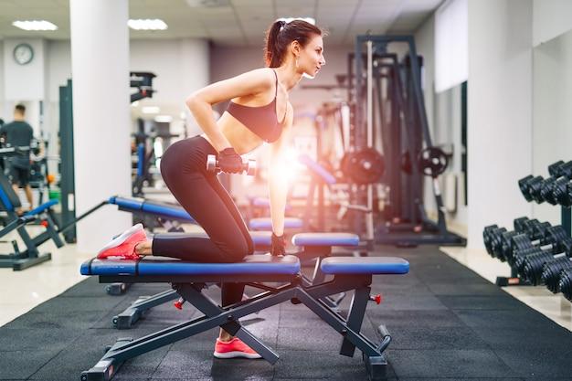 Jonge mooie brunette fitness meisje traint in een sportschool op een sportuitrusting. gezondheidsleven en sportgewoonten concept.