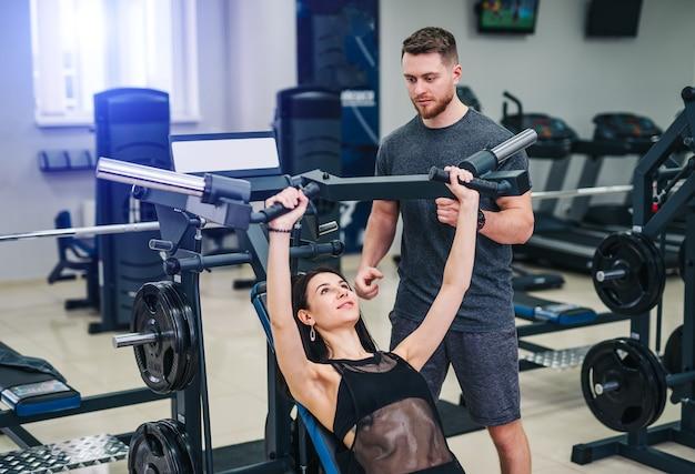 Jonge mooie brunette fitness meisje traint in een sportschool op een sportuitrusting. trainer geeft aanbevelingen voor betere resultaten.