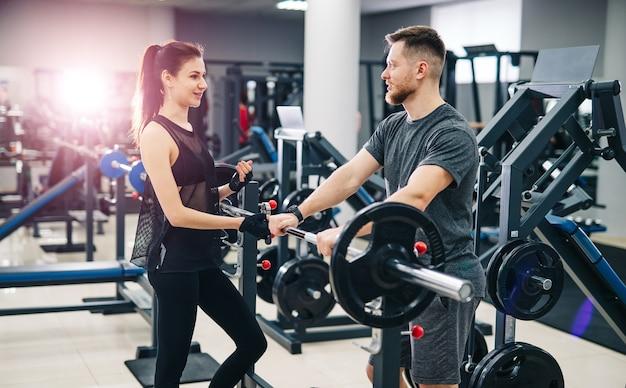 Jonge mooie brunette fitness meisje traint in een sportschool op een sportuitrusting.