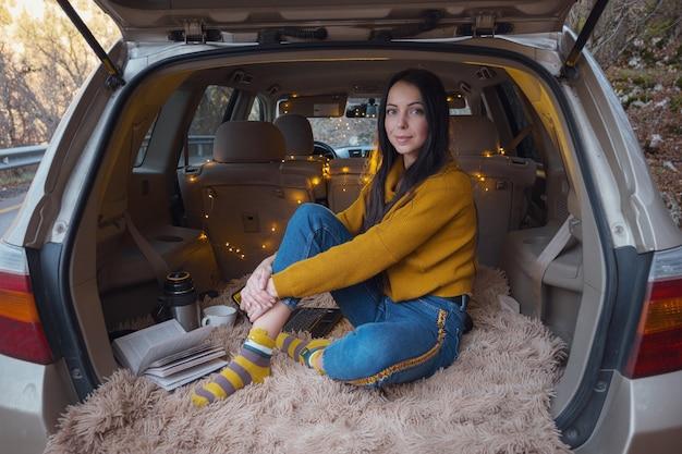 Jonge mooie brunette geniet van ontspannen in de kofferbak van haar auto. een gele slinger en een beige plaid zorgen voor gezelligheid