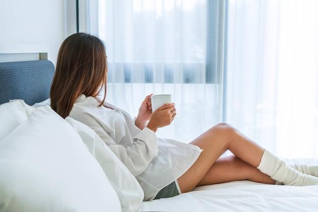 Jonge mooie brunette haar vrouw in wit overhemd pyjama's koffie drinken zittend op het bed in de ochtend.