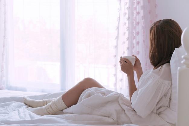 Jonge mooie brunette haar vrouw met een kopje koffie zitten op het bed bij het raam