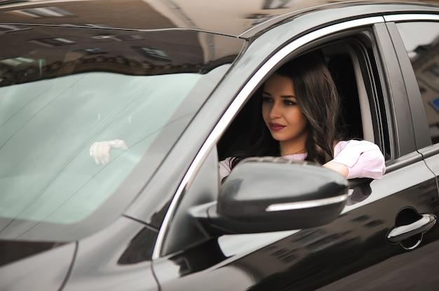 Jonge mooie brunette in de zwarte auto.