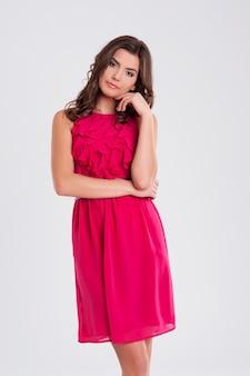 Jonge mooie brunette in een roze jurk