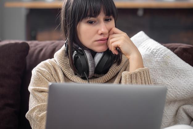 Jonge mooie brunette in koptelefoon in een gezellige trui en kijkt naar het scherm van de laptop.